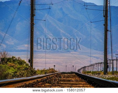 Railway tracks are heading the horizon, towards the mountains in a hot sunny summer day. The last part of the track is blurry due to the mirage.