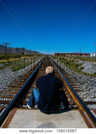 A lonely blond boy in a dark blue blouse, is sitting back to the camera on the grade crossing, looking ahead towards the railway track and surrounding grasslands.