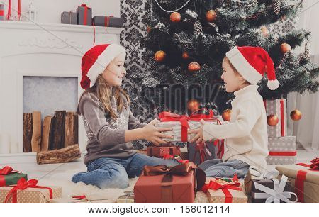 Cute happy excited children, boy and girl in santa hats unwrap christmas present box in beautiful room. Sister and brother give Xmas gifts near decorated tree and fireplace. Family holiday