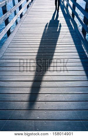 Whole body shadow silhouette of female person seen with the shoes walking at planks of wooden pier above the sea