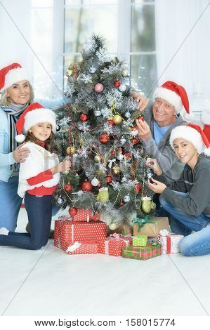 Happy grandparents with grandchildren decorating Christmas tree together