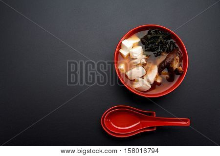 Japanese Miso Soup On A Red Bowl And Spoon On The Table.