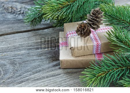 Christmas composition of pine cones spruce branches and two gift boxes with fir cones on the background of old unpainted wooden boards; with copy-space