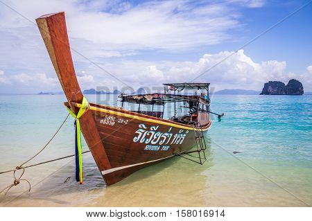 Longtail boat in crystal clear blue waters waiting for passengers on beautiful white beach in Ko Mok, Thailand