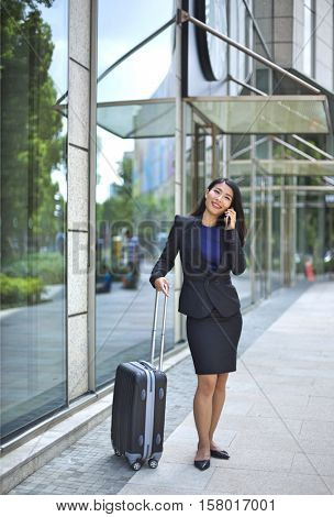Close up of a asian woman waiting with a suit case in an airport or station making a phone call on her mobile telephone