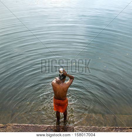 Gokarna, India - January 16, 2016: Unidentified temple brahmin taking bath in sacred lake in Gokarna. The city is a holy pilgrimage site for Hinduists