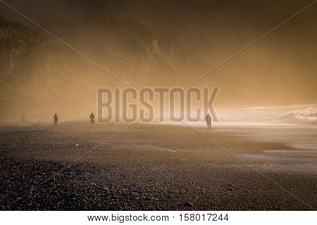 A pebble beach on New Zealand's South Island near Punakaiki is covered in mist as the sun is setting