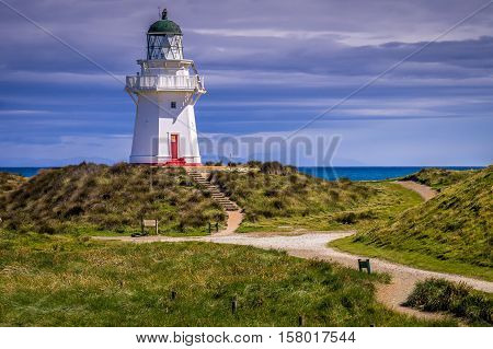 View of lighthouse on hill at Waipapa Point on New Zealand's South Island on a cloudy day