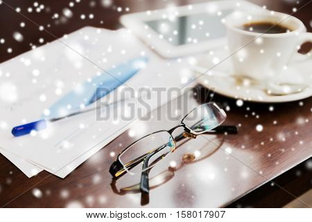 business, eyewear, optics and objects concept - eyeglasses, tablet pc, charts and coffee on office table over snow