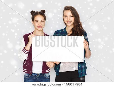 winter, christmas, people, advertisement and holidays concept - happy smiling pretty teenage girls or friends holding and showing white blank board over gray background and snow
