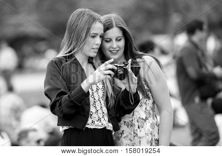PARIS FRANCE - MAY 21 2016: Two young girls admiring the photographs they took on Nikon mirorrless camera in front of Eiffel Tower in Paris - black and white image