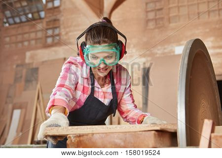 Woman making carpenter apprenticeship and working with grinder