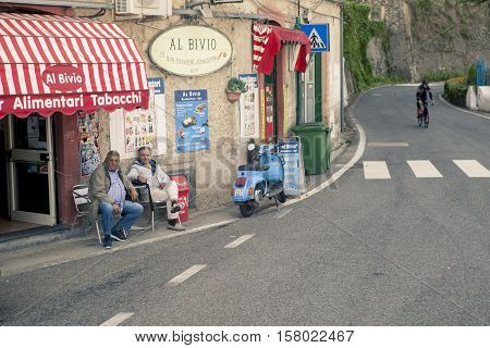 AMALFI COAST LINE SOUTH ITALY - NOVEMBER 5 : unidentified people sitting on desk beside road of amalfi coast line on november 5 2016 in naple amalfi south italy