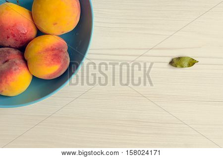 Ripe peaches in blue bowl on white wooden background. Group of fresh peaches on white table. Juicy and fresh peach with place for text. Concept for healthy eating and nutrition. Top view. Copy Space.