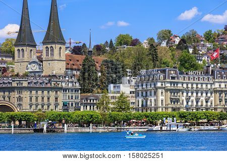 Lucerne, Switzerland - 8 May, 2016: buildings along Lake Lucerne, people in a boat and on the embankment of the lake. Lucerne is a city in central Switzerland, it is the capital of the Swiss Canton of Lucerne.