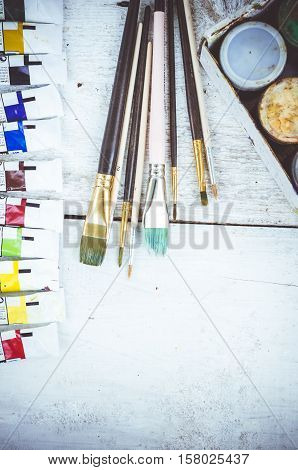 Artist paint brushesoil paint tubes and gouache paint jars on white wooden background. Brush paint artistic. Tools for creative work. Back to school. Paintings Art Concept. Top view. Copy space.