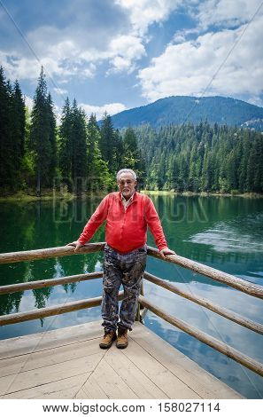 Full length portrait of a handsome senior man in bright sweater near the beautiful forest lake. Looking at the camera. Serious senior man with gray hair and beard on excursion. Vertical image.