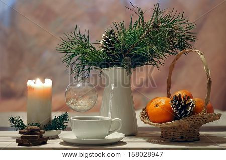 Holiday tea with chocolate. Branches of pine in a jar Christmas transparent ball. Candle beige white cup. Basket with bright tangerines and some chocolate