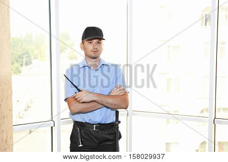 Security man standing beside window