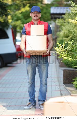 Young male deliverer with boxes outdoors