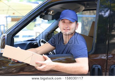 Young male deliverer with box sitting in car