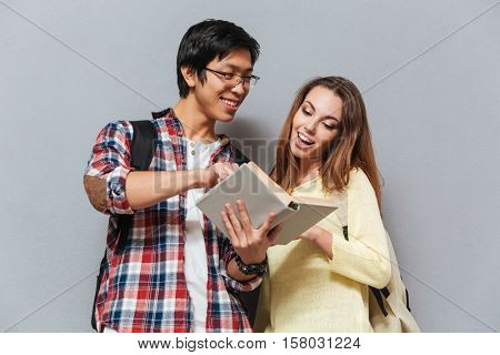 Portrait of a smiling multicultural couple with backpacks reading book isolated on the gray background