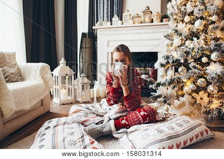 10 years old preteen girl in pajama laying on carpet with holiday bedding by Christmas tree and fireplace and drinking milk in morning at home