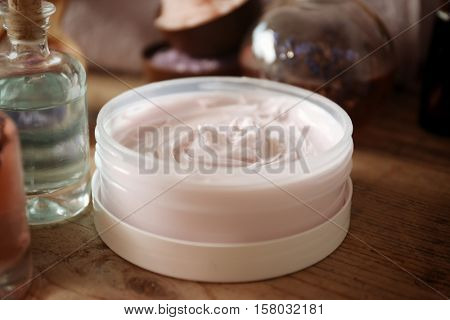 Nourishing cream on wooden table, closeup