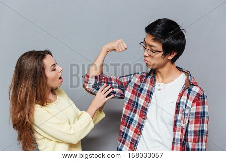 You ng asian guy showing biceps to his girlfriend isolated on the gray background poster