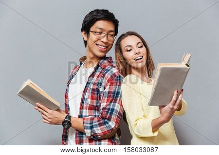 Pportrait of young multicultural couple reading books together isolated on the gray background