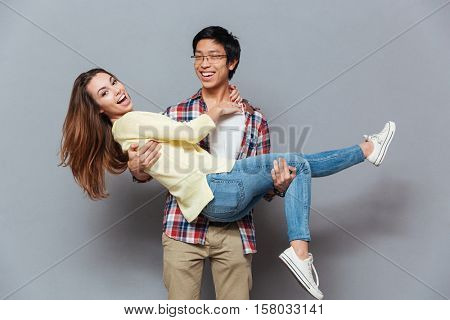 Smiling happy asian guy holding his girfriend in his arms isolated on the gray background