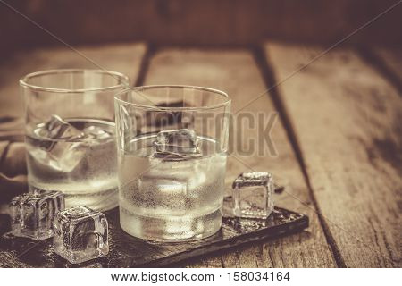 Vodka in shot glasses on rustic wood backgroundcopy space