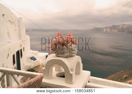White villa house in Oia with stairs and a flower pot, Santorini. Toned Image