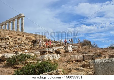 Sounion Greece - Sept 21 2016: Tourists visits the Cape Sounion - Ruins of an ancient Greek temple of Poseidon before sunset under dramatic cloudy sky