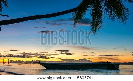 Sunset on Kri Island. Boats under Palmtrees. Raja Ampat, Indonesia. West Papua