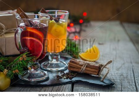 Mulled wine and apple cider in glass cups with spices and decorations