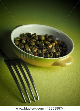 Capers in a rustic ceramic bowl on a green table cloth