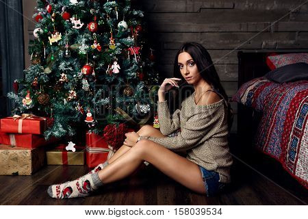 woman with black hair posing under christmas tree with gifts