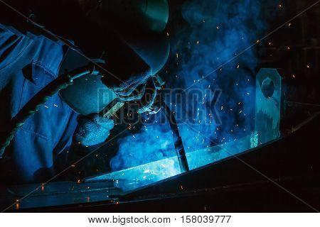 Welder of Metal Welding with sparks in industry steel weld