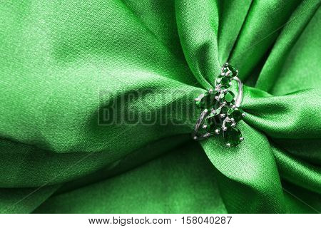 Emerald ring on green crumpled satin as a background