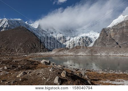 Grey Moraine Lake And Snowy Mountain Peak Covered With Clouds In Himalayas, Nepal. Mirror Water Of A