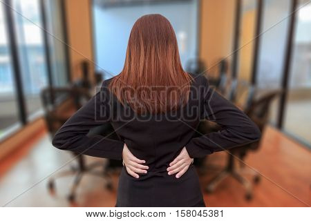 Woman lower back painful injury. Businesswoman backache and injury in meeting room - office syndrome concept