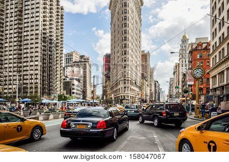 New York City, USA - May 10, 2015: Flat Iron building facade, one of the first skyscrapers ever built, with NYC Fifth Avenue and taxi cabs