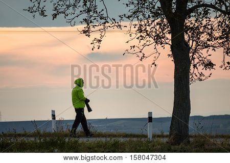 Photographer outdoors walking on road with big zoom lens as professional digital equipment waiting on sunset wearing jaskrawy jacket and gloves.