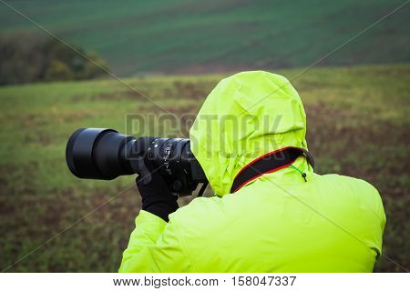 Photographer outdoors with big zoom lens as professional digital equipment getting ready to shoot a photo wearing a bright jacket and gloves.