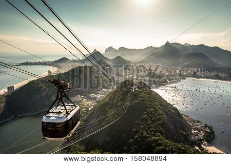 View of Rio de Janeiro city from the Sugarloaf Mountain by sunset with a cable car approaching