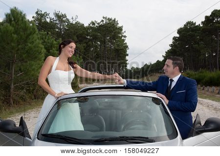 Cheerful Wedding Couple Posing Near Splendid Cabriolet Car