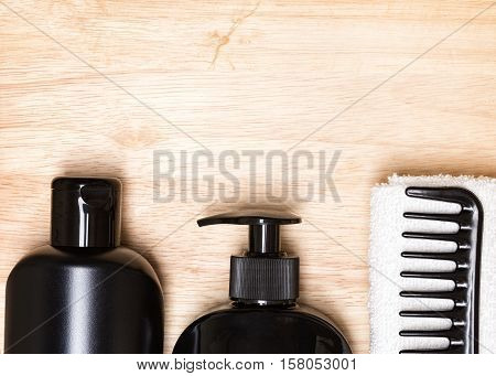 Hair care and styling background. Hair beauty products, wide tooth comb, towel on wooden surface. Copy space