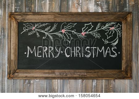 Chalk board with Merry Christmas message , santa and snowflakes on wooden background for a greeting card