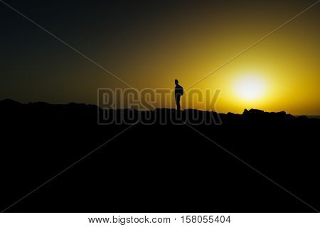 the silhouette of a young caucasian man carrying a backpack in his back at dusk, against a colorful yellow sky, with the horizon and the sun in the background